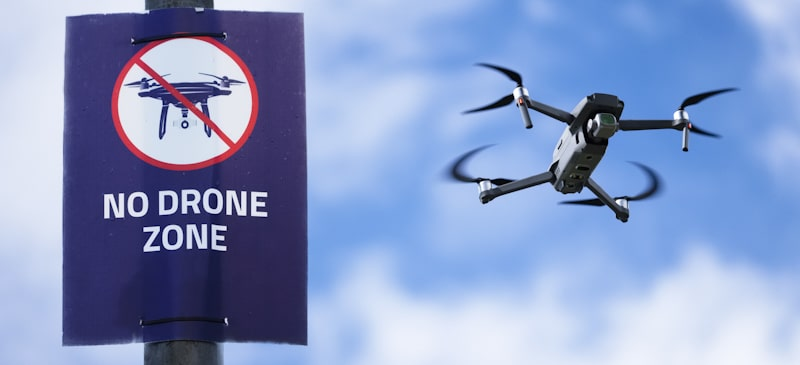 no drone zone sign with drone flying by