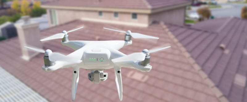 white drone flies over house