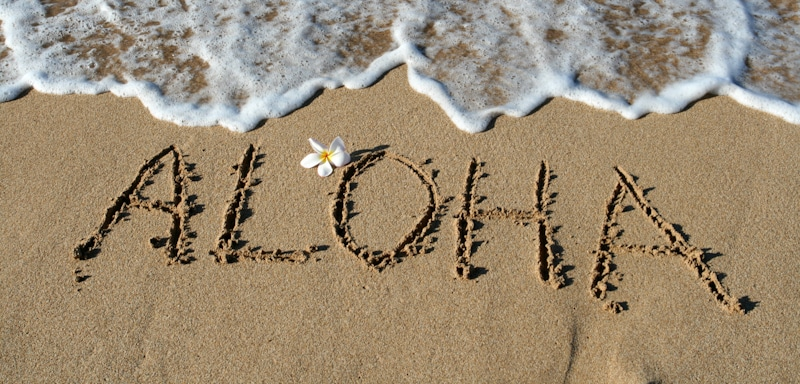 aloha sign written in the sand