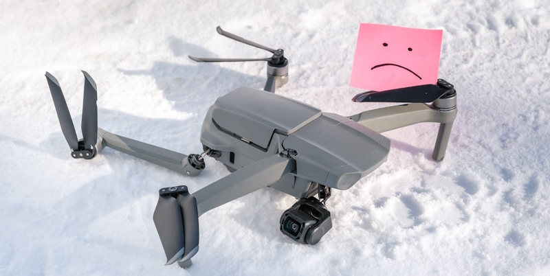 crashed drone in snow with sad smiley face