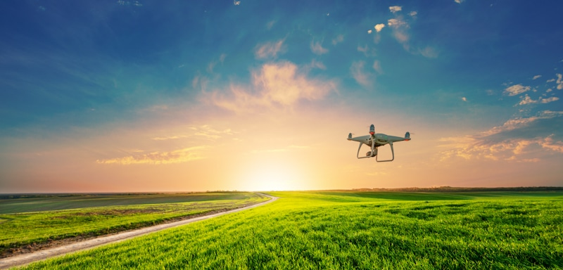 drone flies over open field in sunny day