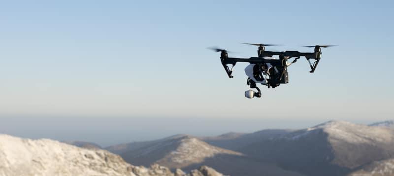 drone flies over snowed peaks