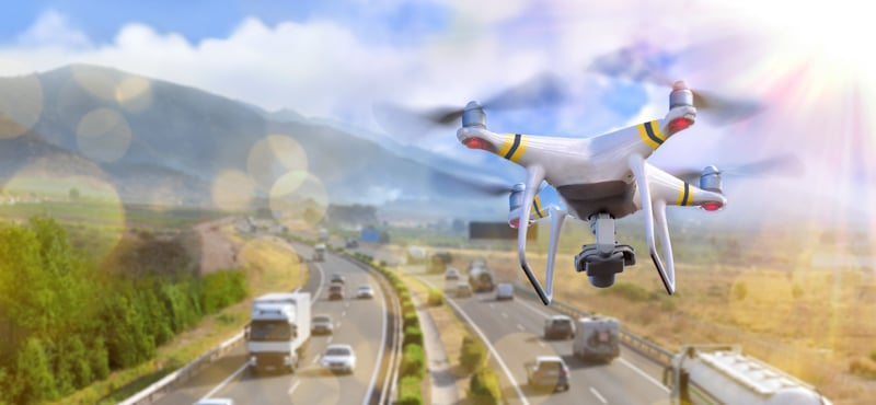 drone flies towards the moving traffic