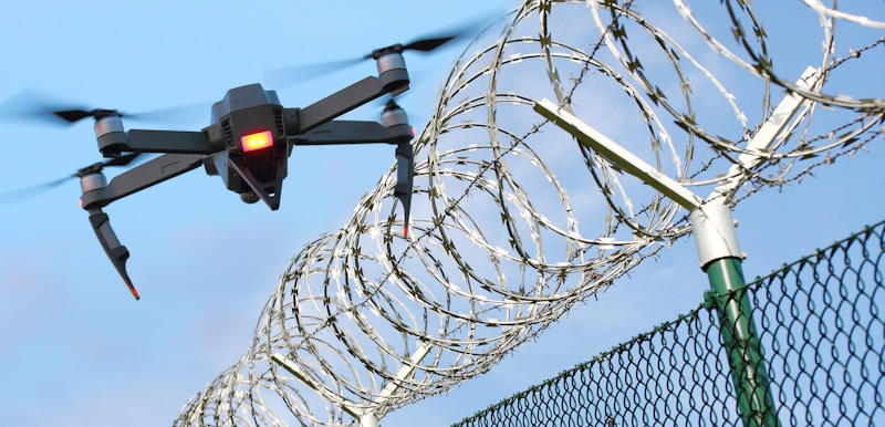 drone flying near barbwire fence