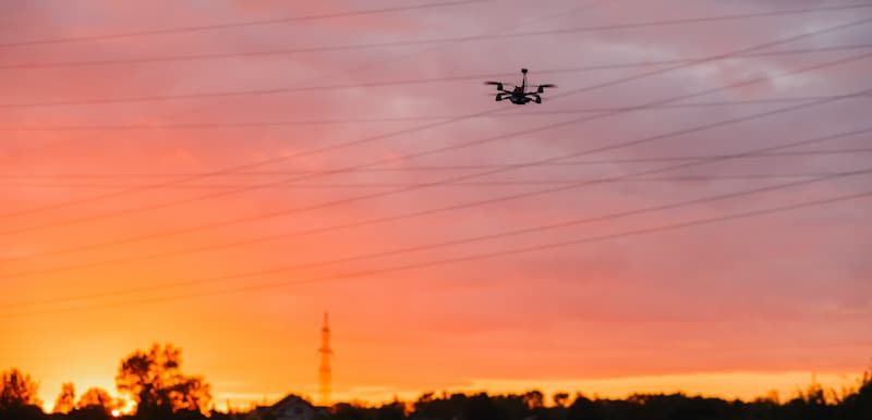 drone flying near power lines in sunset