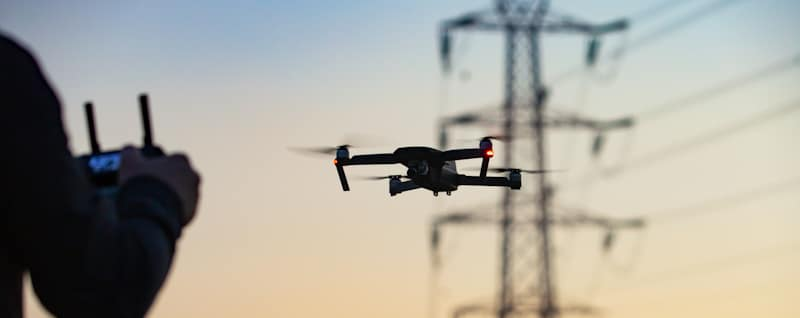 drone hovering in place near powerlines tower