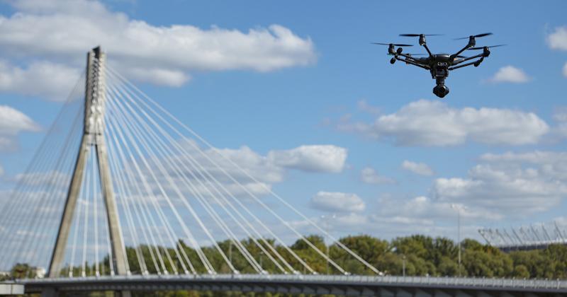 drone quadcopter flies near bridge