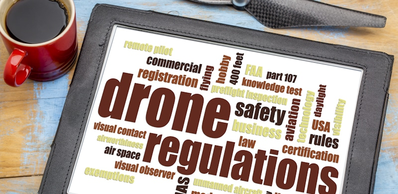 drone regulations sign in tablet next to cup of coffee