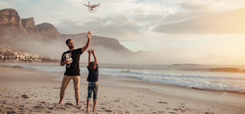 father and son fly drone in the beach