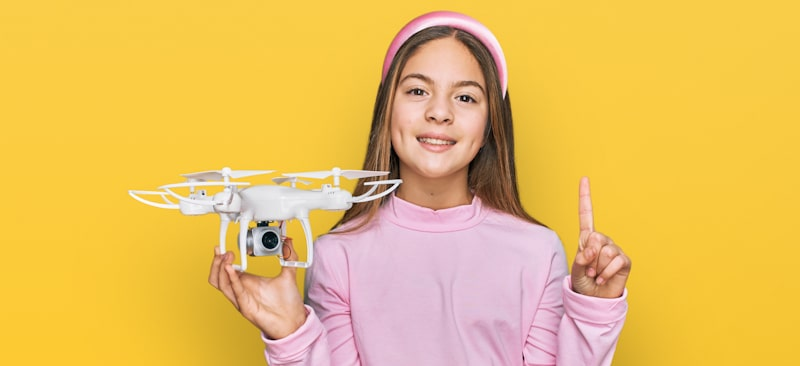 girl holds drone with one hand and points up