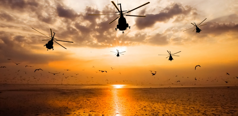 group of helicopters fly out into sunset