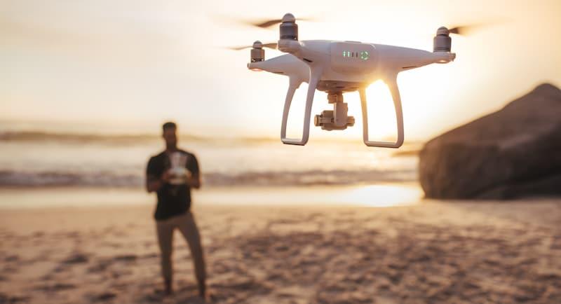 guy flies drone in the beach