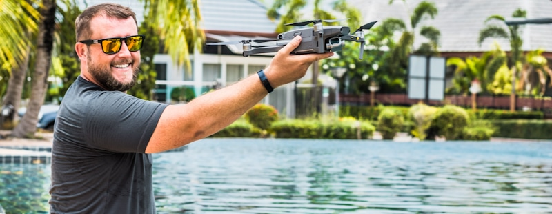 guy holds drone over pool