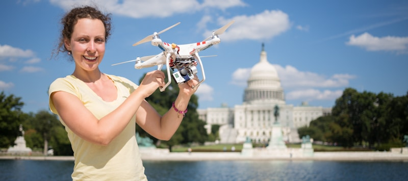 lady holds drone in capitol building area