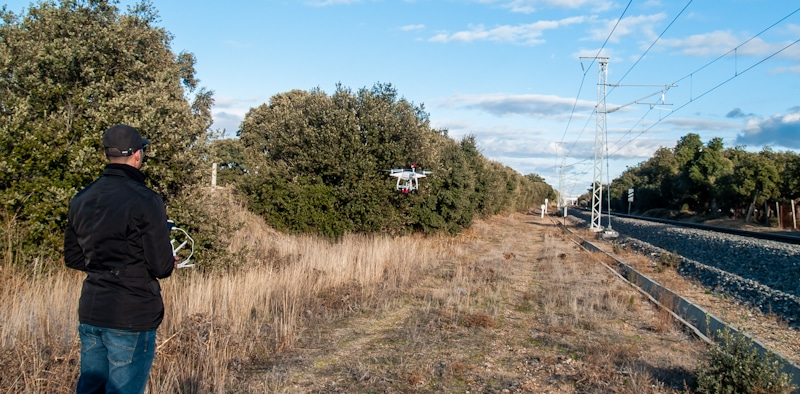 man flies drone near railroad tracks