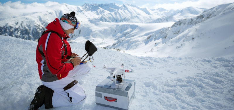 man prepares drone to fly in snow