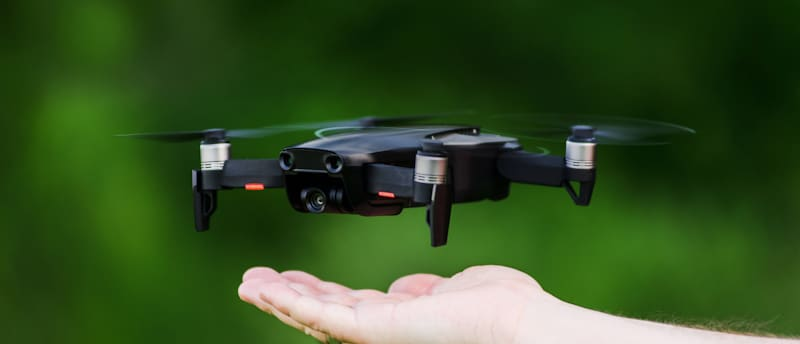 mini drone hovers above pilots hand