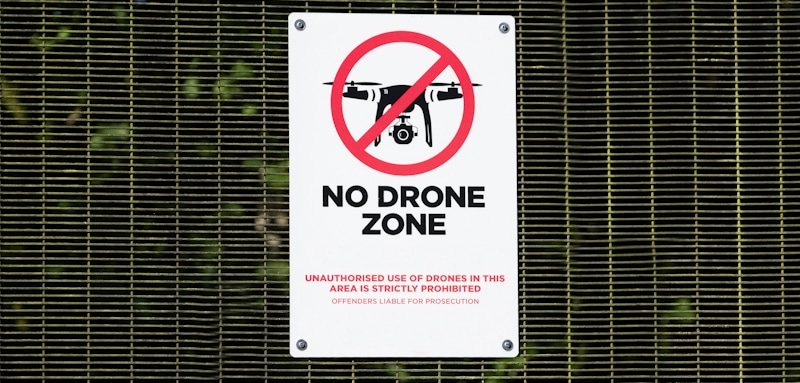 no drone sign in yellow fence