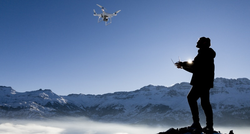 person flying drone in snowed mountains
