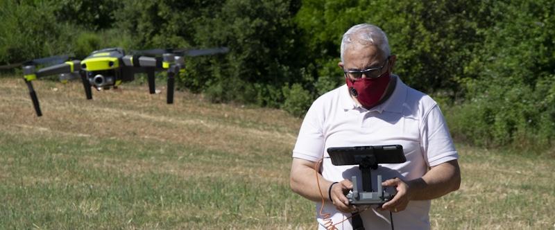 senior male flies drone with ipad