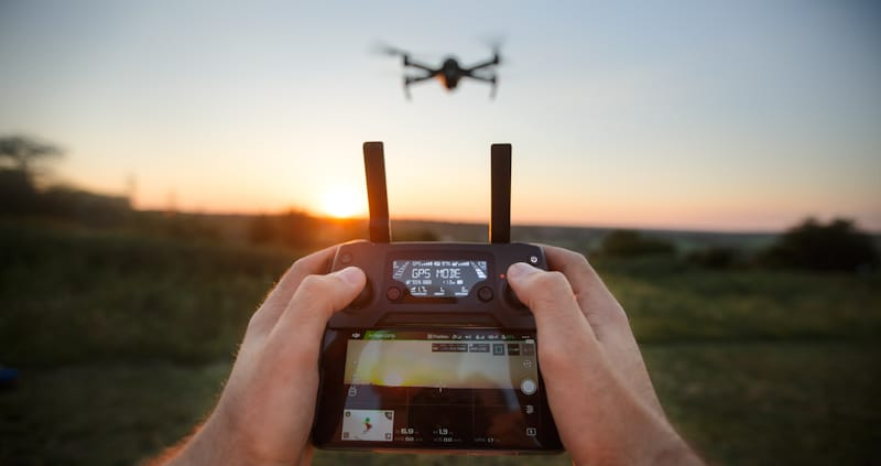 drone being flown with mobile controller
