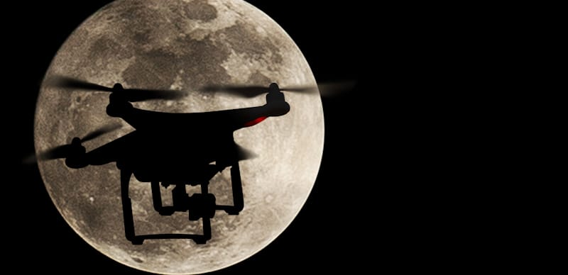 drone flies in front of the moon