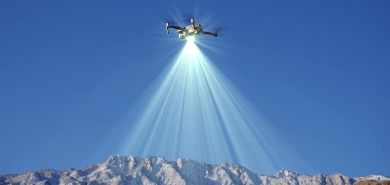 drone flies over snowed in mountain peaks