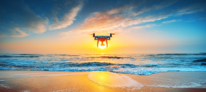 drone hovers on beach shoreline at sunset