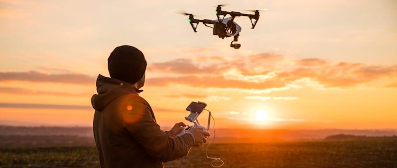 man flies drone at sunset