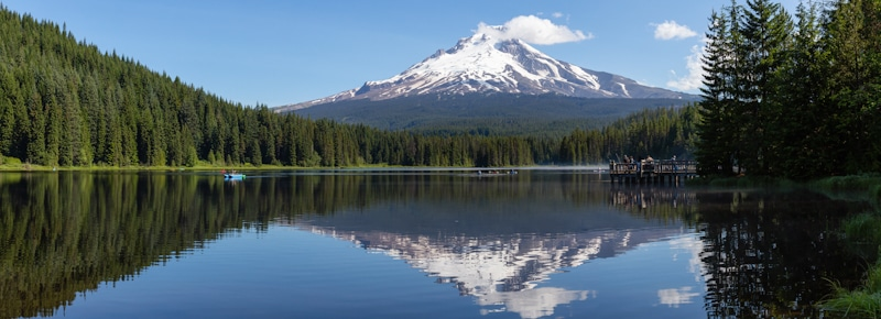 snowy white peaks reflected in lake of national forrest