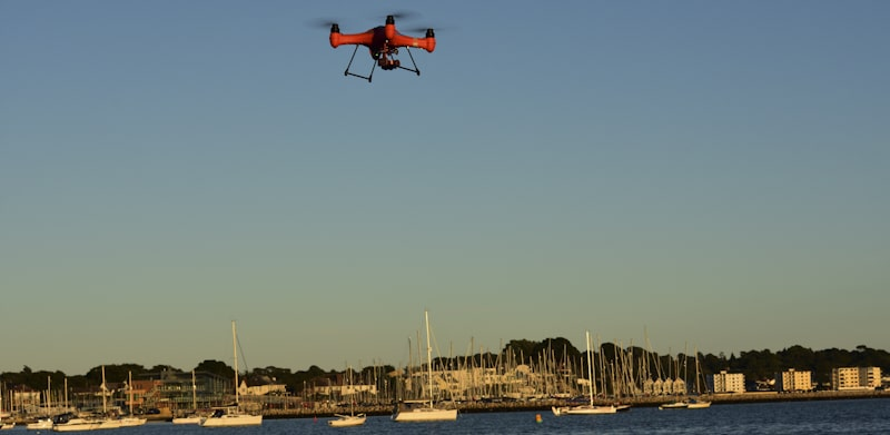 Red drone flies over bay in sunset