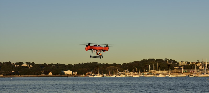 Red drone flies over bay