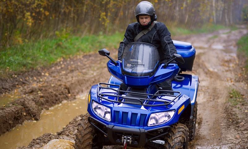 atv on muddy road bogs