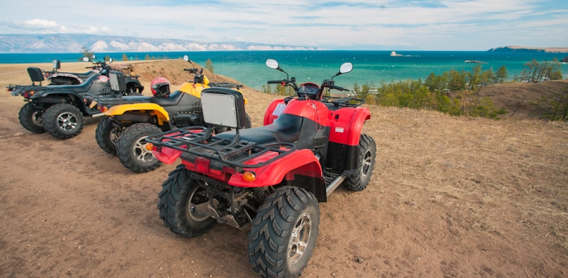 atvs parked in a beach cliff