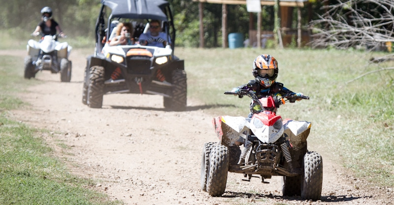 child drives atv in dusty road followed by adults