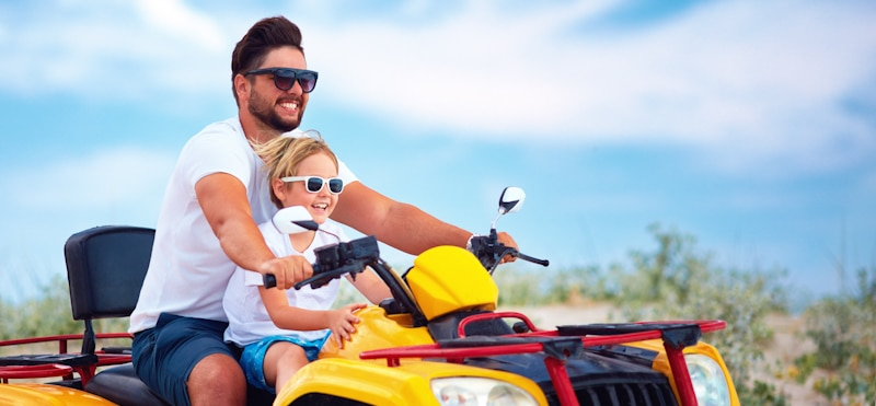 dad and son go for a ride on atv