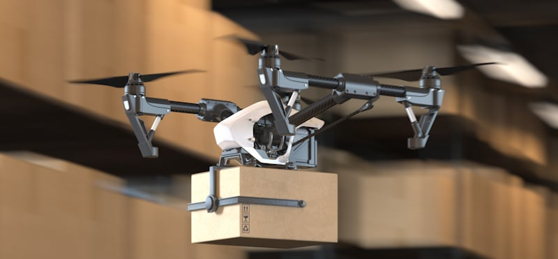 drone carries box out of warehouse