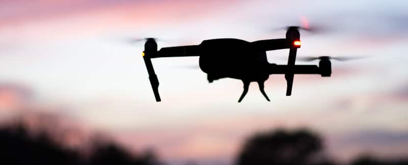 drone in darkening sky with red and yellow lights