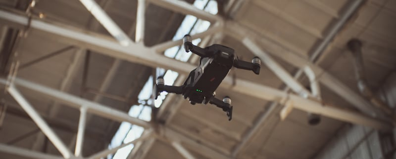 drone shows green lights and hovers inside warehouse
