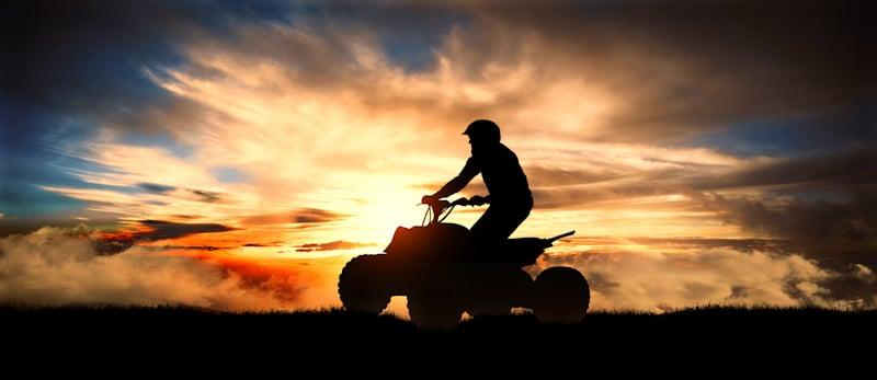 guy drives wheeler in sunset