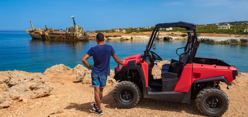 guy stands next to ATV in front of lake