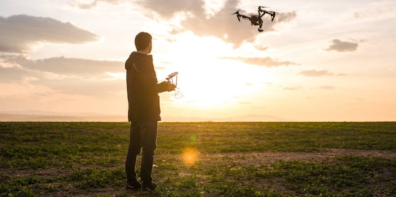 man flies drone in open field
