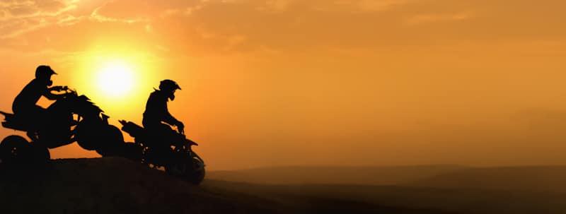 pair of men ride atv in sunset