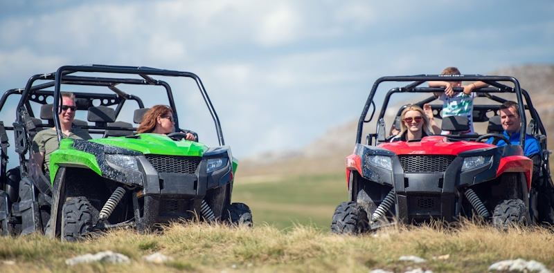 two families ride atvs in a field