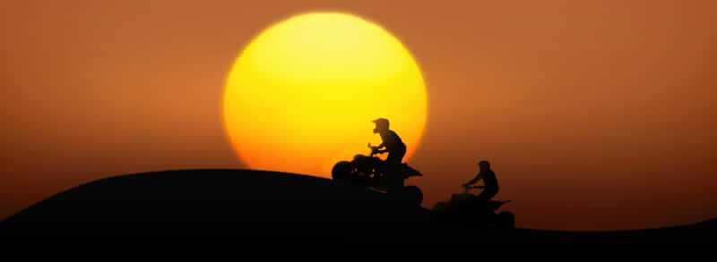 two people ride ATVs up a small hill