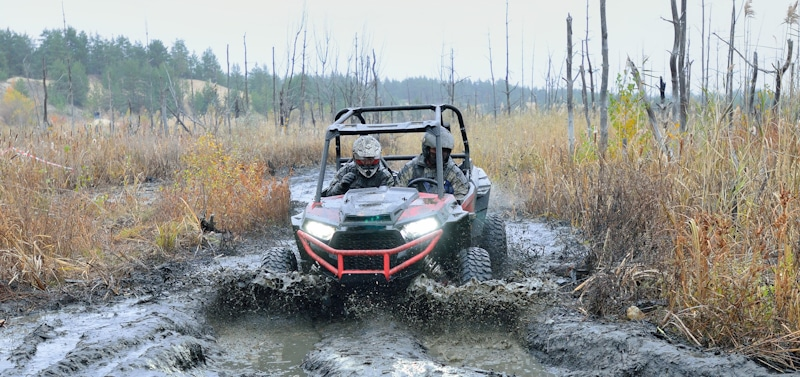 two people ride atv in muddy path