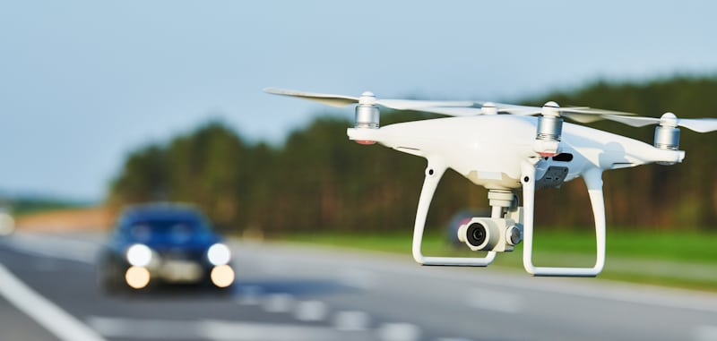 white drone hovers mid road