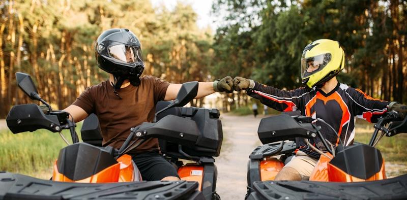 friends ride atv wearing helmets