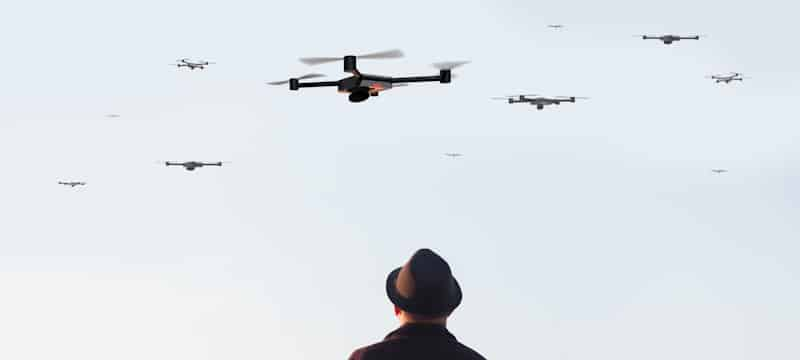 man in hat watches drones fly