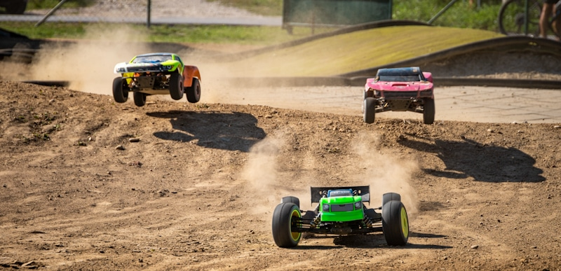 three rc cars in the middle of a race